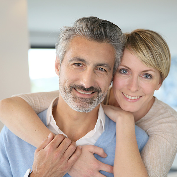 A happy couple hugging and smiling at Hunter Dental Care