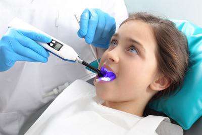 Girl receiving light-cured dental sealants by her dentist in Portland, OR.